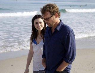 Greg Kinnear e Lily Collins passeggiano sulla spiaggia in Writers