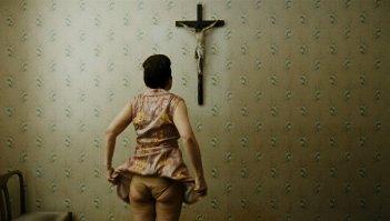 Paradise: Faith, la protagonista del film Maria Hofstätter di spalle guarda un crocefisso in una scena del film