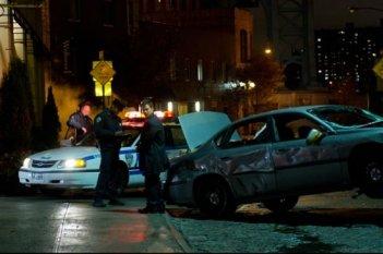 Mark Wahlberg e la polizia esaminano il teatro di un incidente stradale in una scena di Broken City