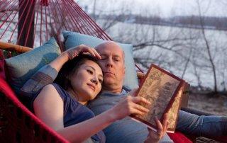 Bruce Willis e Qing Xu si abbracciano su un'amaca in una scena di Looper