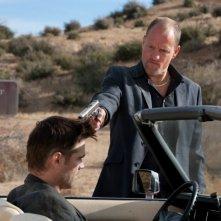 Woody Harrelson punta una pistola alla testa di Colin Farrell in una scena di Seven Psychopaths