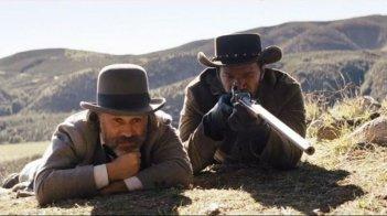 Christoph Waltz e Jamie Foxx appostati in una scena di Django Unchained