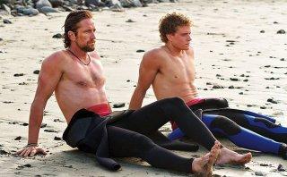 Gerard Butler e Jonny Weston seduti sulla sabbia in Chasing Mavericks