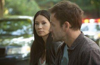 Jonny Lee Miller con Lucy Liu in una scena dell'episodio The Rat Race della serie TV Elementary