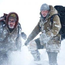 Liam Neeson in fuga dai lupi insieme ai suoi compagni in una scena di The Grey
