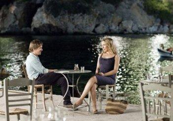 Ethan Hawke e Julie Delpy conversano seduti a un tavolo sulla riva del mare in un'immagine di Before Midnight