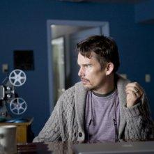 Ethan Hawke guarda un filmato con il proiettore in una scena dell'horror Sinister