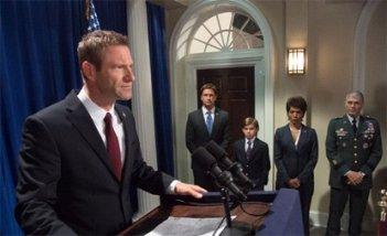 Attacco al potere - Olympus Has Fallen: Aaron Eckhart tiene un discorso. Sullo sfondo il suo staff capitanato da Gerard Butler e Angela Bassett