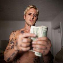 Ryan Gosling conta i soldi del suo bottino in una scena di Come un tuono