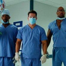 Anthony Mackie, Mark Wahlberg e Dwayne Johnson vestiti da medici in una scena di Suda e cresci