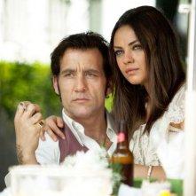Blood ties: Mila Kunis seduta sulle ginocchia di Clive Owen in una scena del film