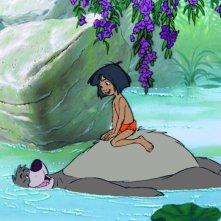 Il libro della giungla: il piccolo Mowgli con l'amico orso Baloo in una scena