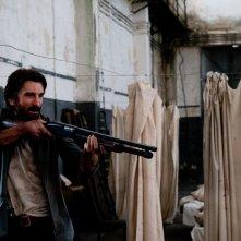 Open Grave: Sharlto Copley punta il suo fucile in una scena del film