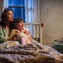 Lili Taylor col piccolo Joey King in una scena di L'Evocazione - The Conjuring