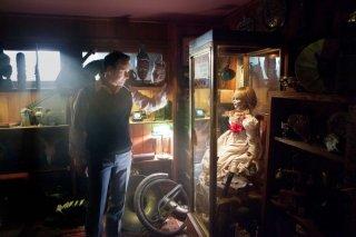 Patrick Wilson osserva una bambola conservata in una teca in una scena de L'Evocazione - The Conjuring