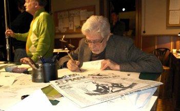 Che strano chiamarsi Federico: il maestro Ettore Scola sul set del film con una copia del giornale Marc'Aurelio