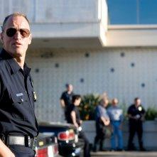 Il poliziotto Woody Harrelson appoggiato alla sua auto in Rampart