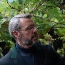 Vinodentro: Lambert Wilson intento a esaminare l'uva del vigneto