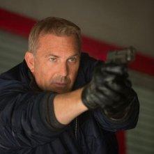 Jack Ryan - L'iniziazione: un primo piano di Kevin Costner con la pistola in pugno