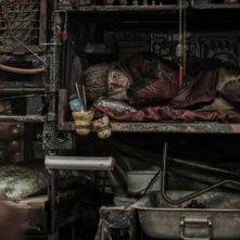 Snowpiercer: Jamie Bell rannicchiato in una cuccetta in una scena del film