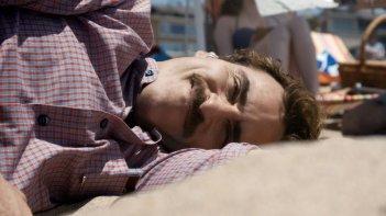 Lei: Joaquin Phoenix sdraiato sulla spiaggia in una scena del film