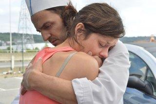 Due giorni, una notte: Fabrizio Rongione abbraccia Marion Cotillard in una scena del film