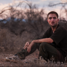 The Rover: Robert Pattinson seduto nella polvere in una scena del film