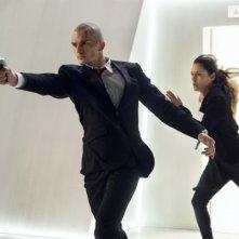 Hitman: Agent 47, Rupert Friend sfodera la pistola, mentre Hannah Ware corre insieme a lui