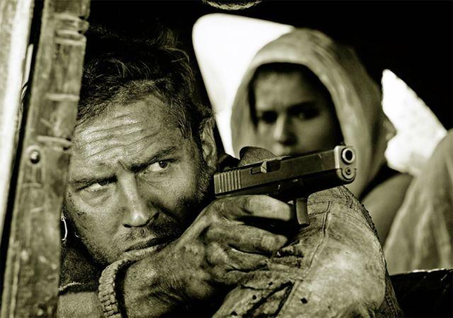 Mad Max: Fury Road - Un primo piano di Tom Hardy menytre impugna la pistola