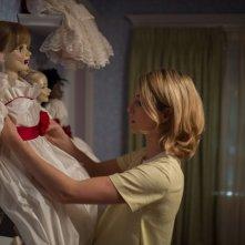 Annabelle Wallis con la sua bambola in una scena dell'horror Annabelle