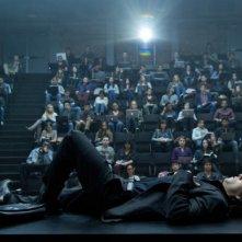 The Gambler: Mark Wahlberg sdraiato su una scrivania di fronte a una folla di studenti