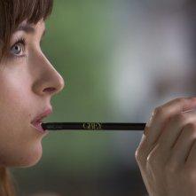 Cinquanta sfumature di grigio: Dakota Johnson tiene una matita in bocca mentre riflette