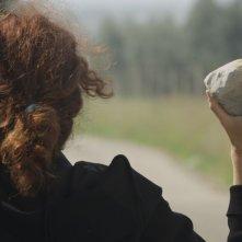 N-Capace: Eleonora Danco (di spalle) impugna una pietra in una scena del film