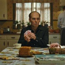 Black Mass - L'ultimo gangster: Johnny Depp gioca a carte seduto a tavola in una scena del film