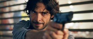 L'esigenza di unirmi ogni volta con te: un primo piano di Marco Bocci con una pistola in mano