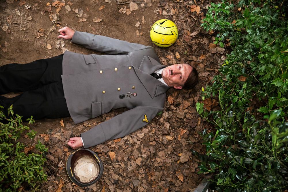 Lui è tornato: Oliver Masucci steso a terra da una pallonata in una scena del film