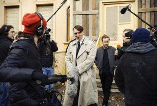 Lui è tornato: Oliver Masucci circondato dalla stampa in una scena del film