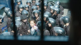 Clash: una donna circondata da poliziotti in una scena del film