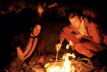 Belli e dannati: River Phoenix e Keanu Reeves davanti a un fuoco in una scena del film