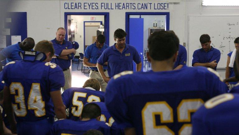 Friday Night Lights: il coach Taylor parla alla squadra, alle sue spalle il suo motto leggendario