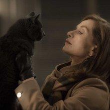 Elle: una assorta Isabelle Hupper con un gatto in un momento del film
