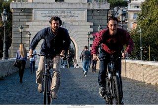 Questione di karma: Elio Germano e Fabio De Luigi corrono in bicicletta in una scena del film