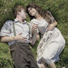 La storia dell'amore: Gemma Arterton e Mark Rendall sdraiati sull'erba in una scena del film